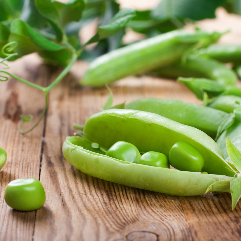 Fresh green peas on old wooden background. Selective focus. Healthy food concept.